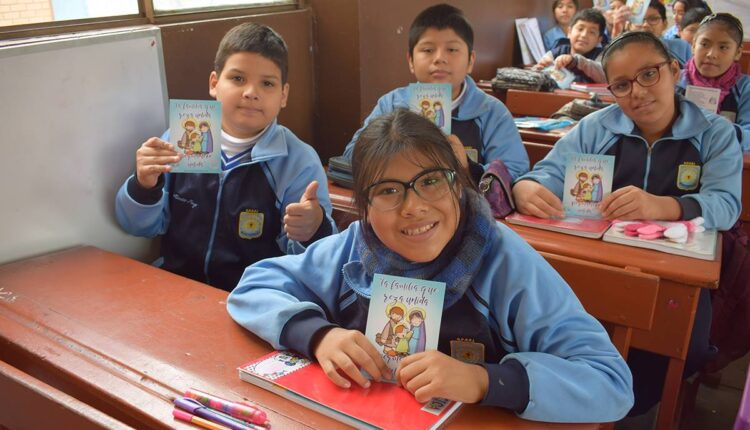 Peruvian students with prayer books created by Family Rosary Peru.
