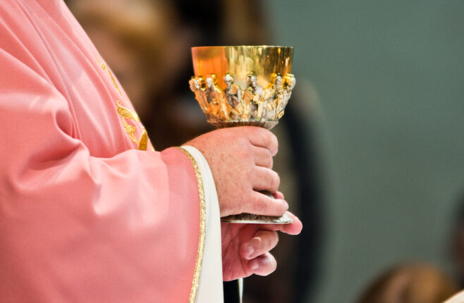 consecration of wine in the hands of the priest who addresses the faithful
